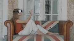 Young woman with with VR device at home touching something invisible Stock Footage