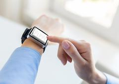 Close up of hands with coding on smart watch Stock Photos