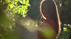 Portrait of pretty brunette girl in red dress in the park. Slow motion video Stock Footage