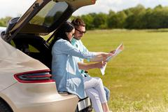 Happy man and woman with road map at hatchback car Stock Photos