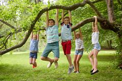 Happy kids hanging on tree in summer park Stock Photos