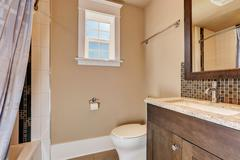 Warm peach walls of half bathroom interior. Mahogany vanity cabinet with gran Stock Photos