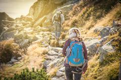 Tourists trekking in high mountains in sunset Stock Photos