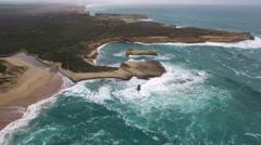 Cinematic drone flight over rugged coastline towards Mutton Bird Island Stock Footage