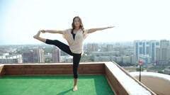 Yoga and meditation in a modern city. Young woman doing yoga on the roof. 20s Stock Footage