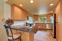 Maple kitchen cabinetry, granite counter top, steel appliances and tile floor Stock Photos