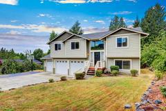Exterior of Two story clapboard siding house with three garage spaces and dri Stock Photos