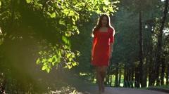 Pretty caucasian brunette girl in red dress walking along sunny park alley. Slow Stock Footage