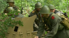 Soldiers roll a anti tank gun through a forest Stock Footage