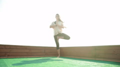 Young woman doing yoga on the mat on the roof. 20s. 4k Stock Footage