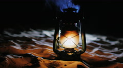 Vintage oil lamp standing on the sand, shines in the dark Stock Footage