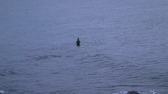 Man fishing in ocean at high tide - wide Stock Footage