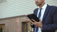 Serious businessman using tablet and smoking cigarette outdoor. 4K Stock Footage