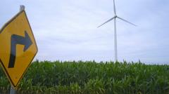 Road sign pointing to wind turbine. Wind turbine on farm field Stock Footage