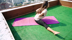 Beautiful woman doing a yoga exercise on he rooftop of a skyscraper. 20s. 1080p Stock Footage