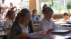 Girls and Boys Sit at School Desks and Read Books Stock Footage
