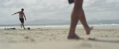 Tourists playing football on beach Stock Footage