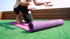 Close-up of young woman unfolding mat for yoga practice. 1080p Slow Motion Stock Footage