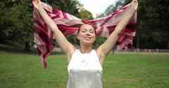 Caucasian woman in a park walking smiling happy face slow motion waving scarf Stock Footage