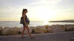 Woman walking at sunset on beach 4K Stock Footage