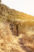 Couple running down a dusty path in full sun light from far away in full sun  Stock Photos