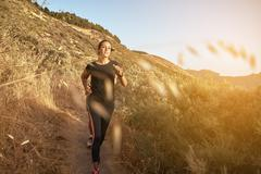 Young woman running down a mountain in full sun light with drying grass behin Stock Photos