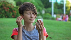 Beautiful young girl listening to music in city park. Stock Footage