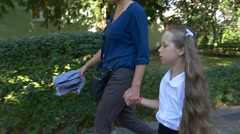 The Little Girl Walks on the Residential Areas With the Mum Stock Footage
