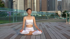 Smiling woman seated in yoga pose on amazing modern city background. Stock Footage