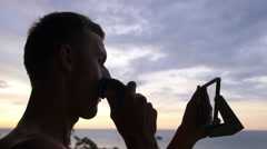 Young Man Shaving with Electric Shaver Outdoors with Sea View Stock Footage