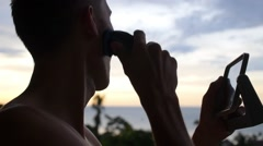 Man Shaving Beard with Electric Razor Against Ocean in Morning Stock Footage