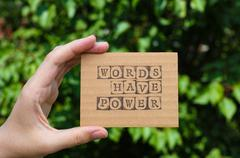 Woman hand holding cardboard card with phrase Words Have Power Stock Photos
