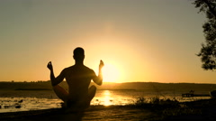 Silhouette of young man practicing meditation on the beach at sunset. 4K Stock Footage