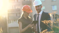 Architect and foreman checking construction project on tablet outdoor on sunset Stock Footage