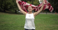 Caucasian woman in a park walking smiling happy face waving scarf Stock Footage
