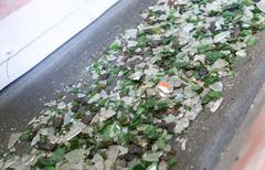 Glass waste in recycling facility. Glass particles in a machine Stock Photos