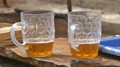 Two glasses of beer on a table outside the slow motion video Stock Footage