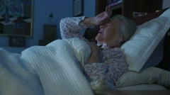An elderly woman lying in bed rubs head in pain Stock Footage