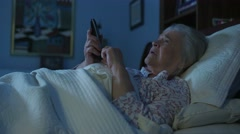 An elderly senior woman in bed struggles with Alzheimers Stock Footage