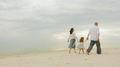 Happy family together walking along the shore of a calm sea. Mom dad and Stock Footage