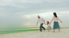 Happy family of three people running on the beach. Fun games with children Stock Footage