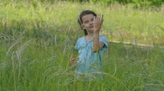 Girl in a meadow in summer hobbling slow motion video Stock Footage