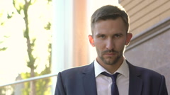Serious man looking strongly at camera and going away. Slowly Stock Footage