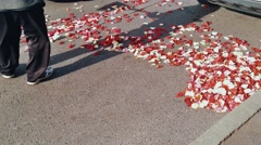 Man with a broom sweeps the rose petals off the sidewalk Stock Footage