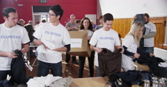 Attractive young charity volunteers are sorting through clothing Stock Footage