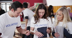 Friendly voluntary workers standing at a soup kitchen Stock Footage