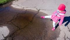 Little girl in a pink coat, jeans and boots walking the park Stock Photos