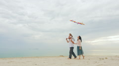 Friendly young family playing with daughter, fly a kite. Against the backdrop of Stock Footage
