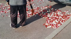 Man with a broom sweeps the rose petals off the sidewalk. 4K Stock Footage