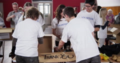 "One male and one female charity volunteers of mixed ages hold up a ""Thank You"" Stock Footage"